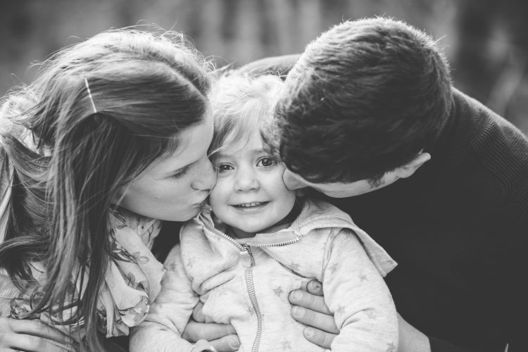 Aberdeenshire Family Photographer Family Session at Leith Hall parents kissing little girl on the cheeks
