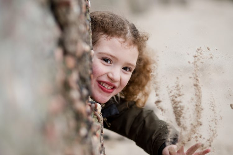 Aberdeenshire Family Photographer Family Session at Sandend Beach little girl throwing sand and smiling