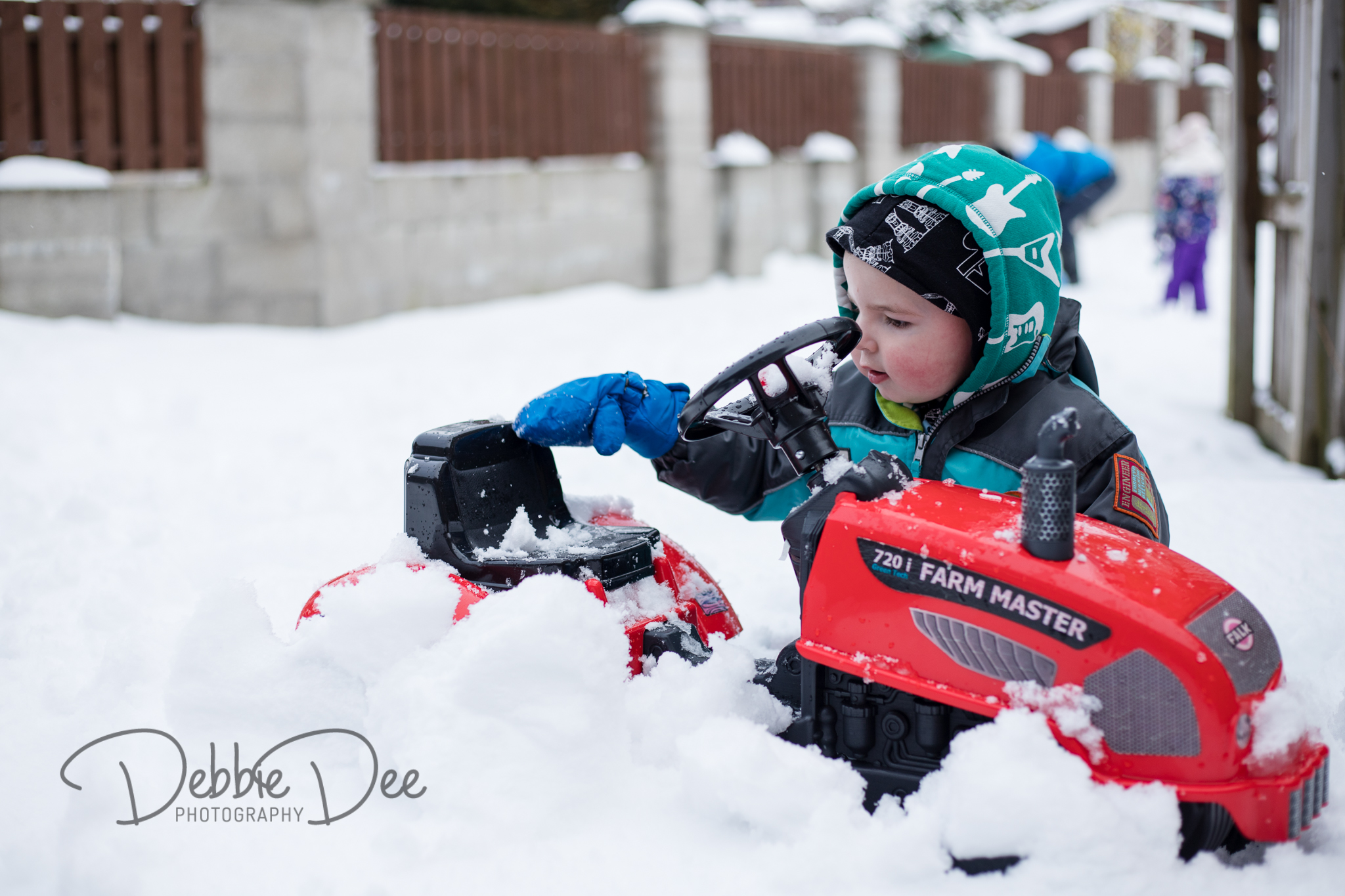 Boy playing with toy tractor in the snow
