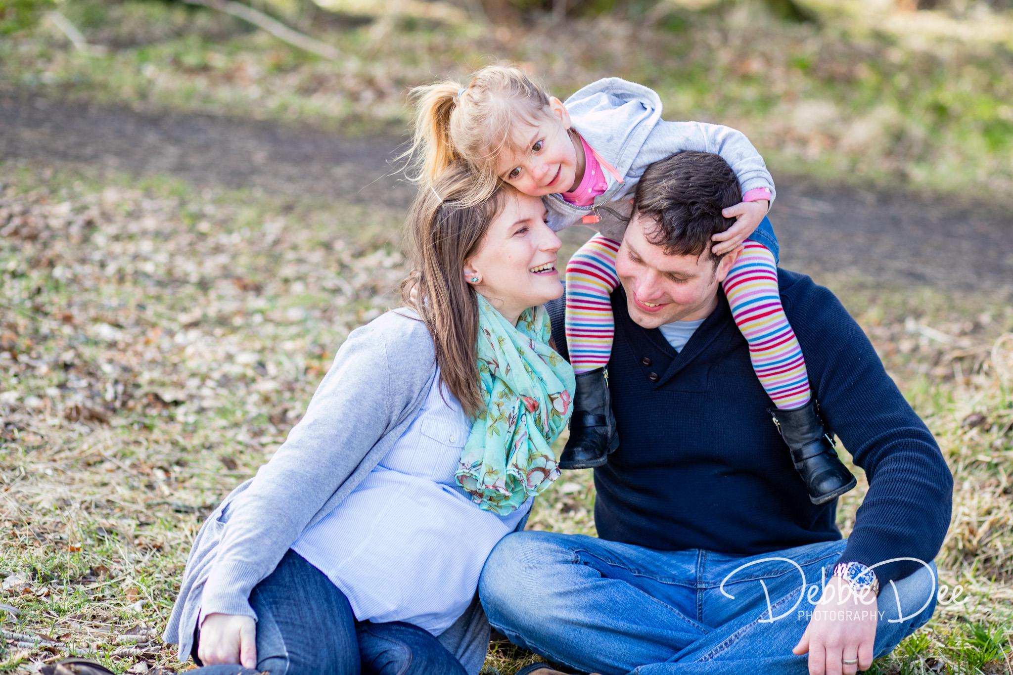 Aberdeenshire Family Maternity Photography Session Mum Dad and little girl cuddling together on the ground