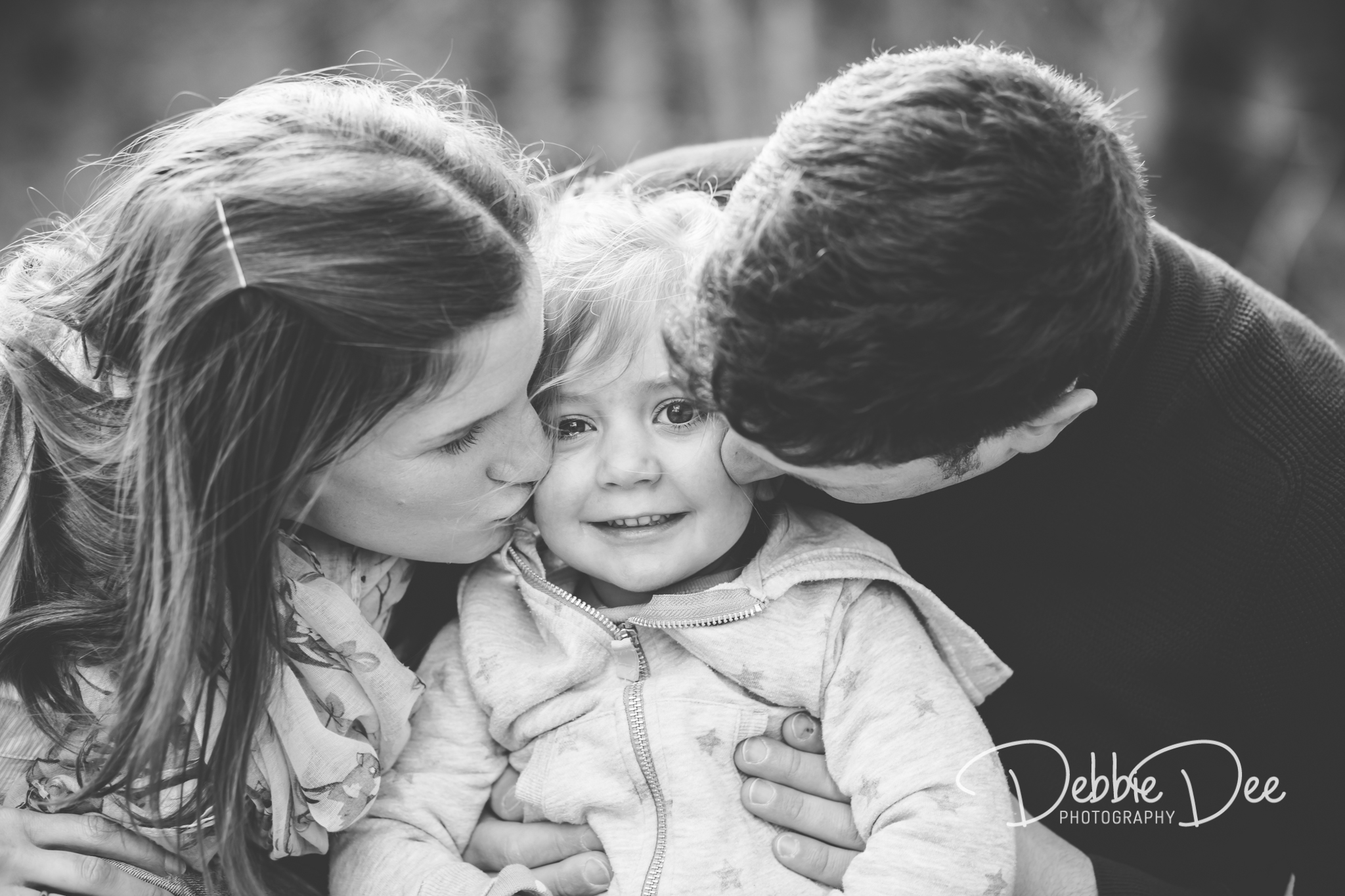 Family Maternity Photography Session Mum and Dad kissing little girl on the cheeks