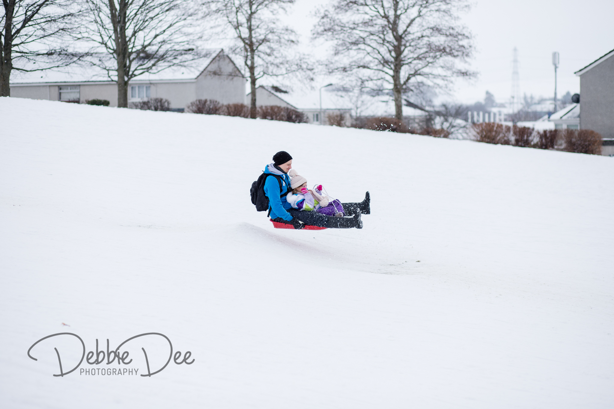 Dad and daughter sledging over ramp