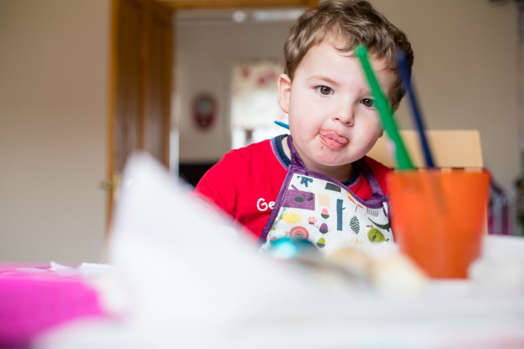 Aberdeenshire Family Photographer Debbie Dee Photography In-Home Lifestyle Photography - child painting with tongue sticking out