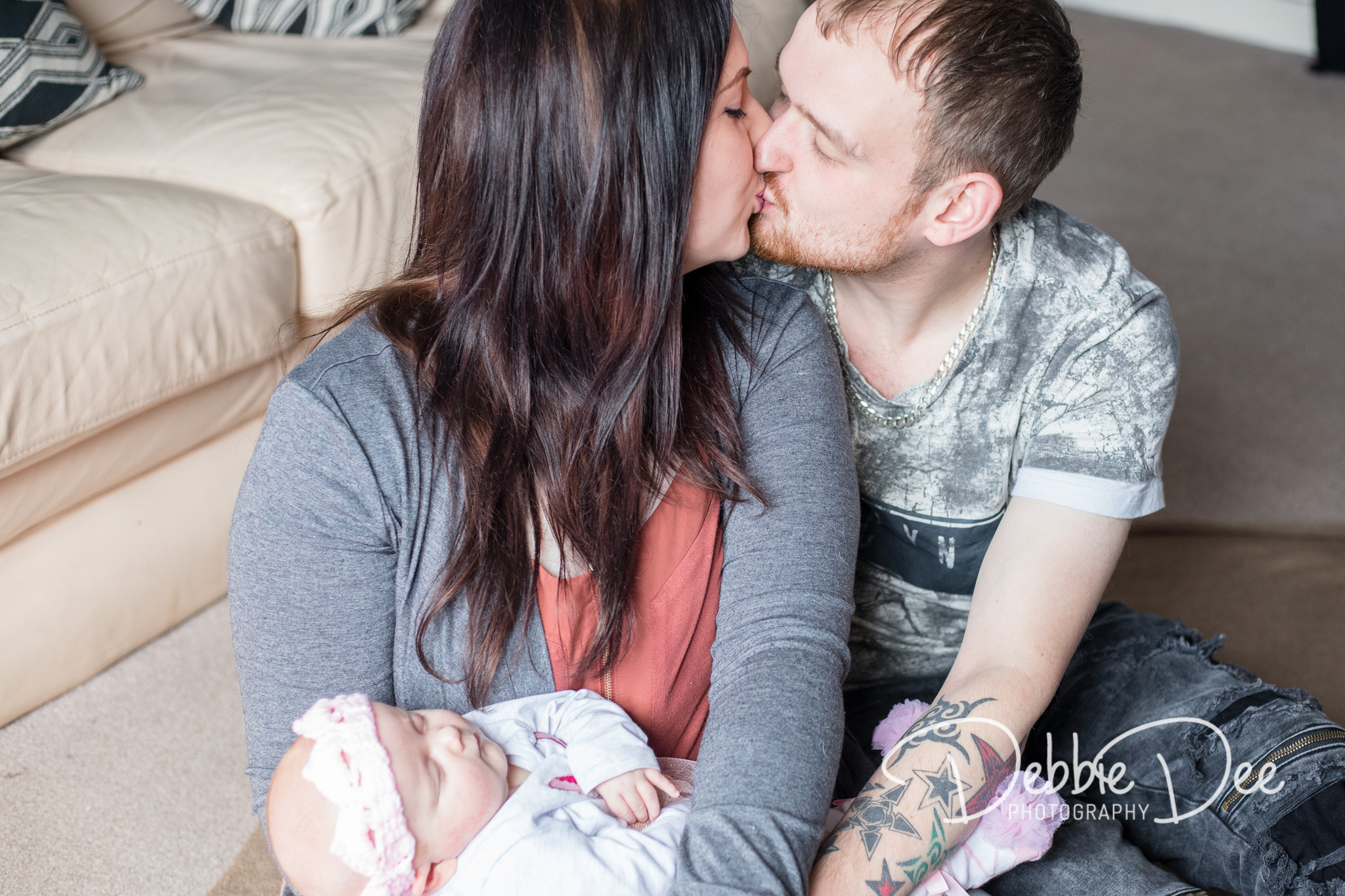 Family photography in-home lifestyle session aberdeenshire Debbie Dee Photography mum and dad kissing while holding baby