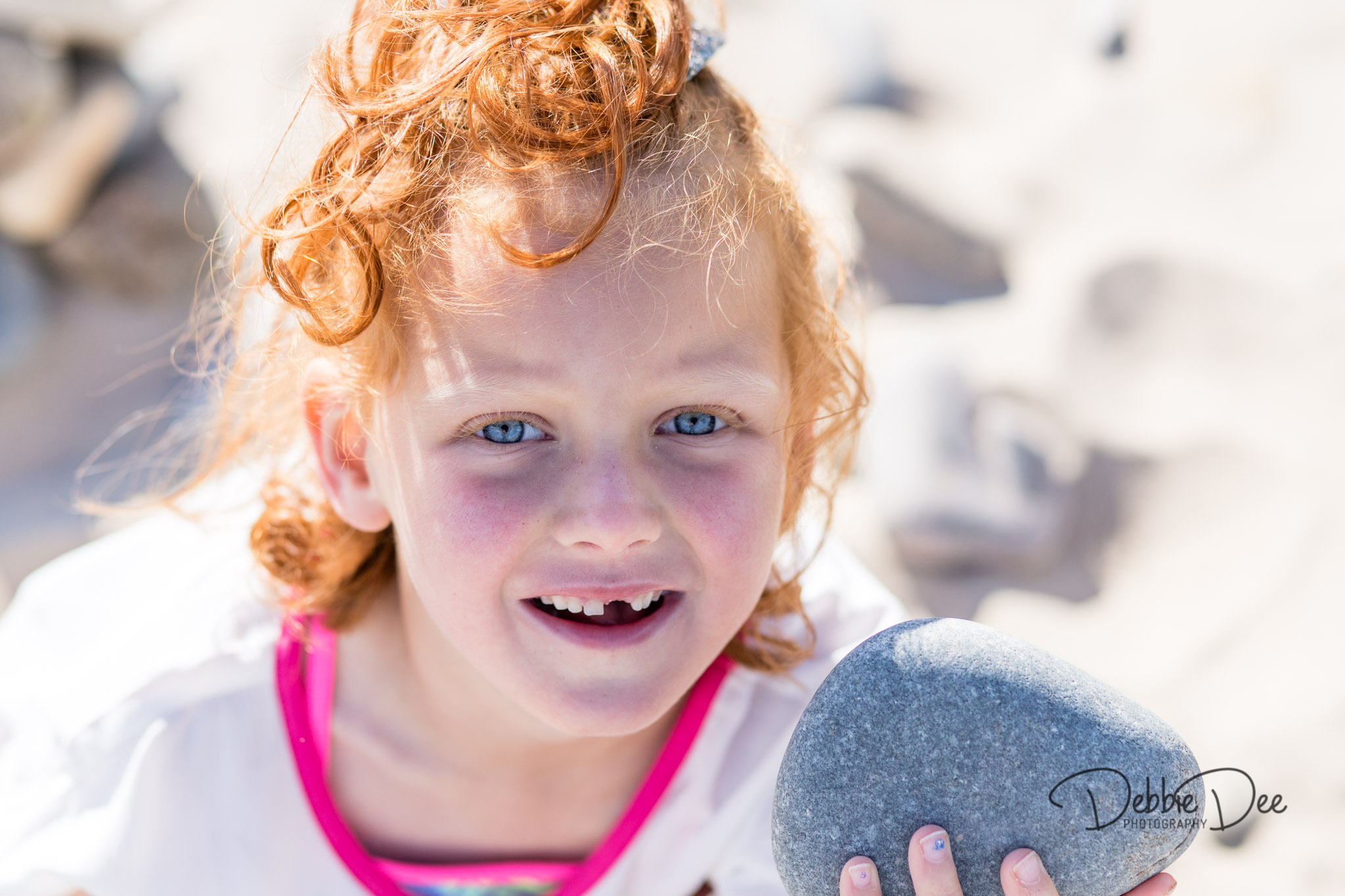Family photography session banff beach aberdeenshire Debbie Dee Photography girl smiling holding rock