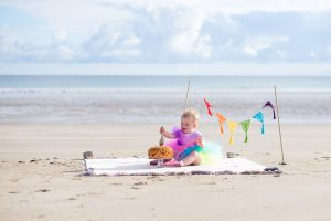 One year cake smash photo session on the beach - rainbow flags and one year old holding spoon over rainbow cake - Debbie Dee Photography
