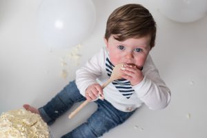 One year cake smash and splash photo session - boy looking up with wooden spoon covered in cake in his mouth - Debbie Dee Photography Aberdeen Aberdeenshire Moray
