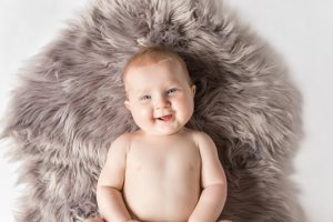 Overhead shot of six month old baby on grey rug smiling up - sitter session aberdeenshire - Debbie Dee Photography