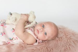 Six month old child laying on pink rug looking to camera holding toy bunny - sitter session aberdeenshire - Debbie Dee Photography