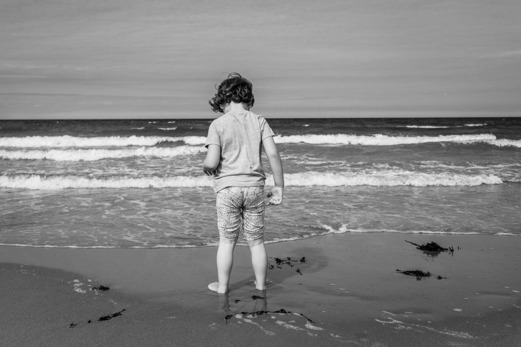 Black and white photo of boy from the back staring out to sea at Sandend Beach aberdeenshire - Debbie Dee Photography - Aberdeenshire family photography