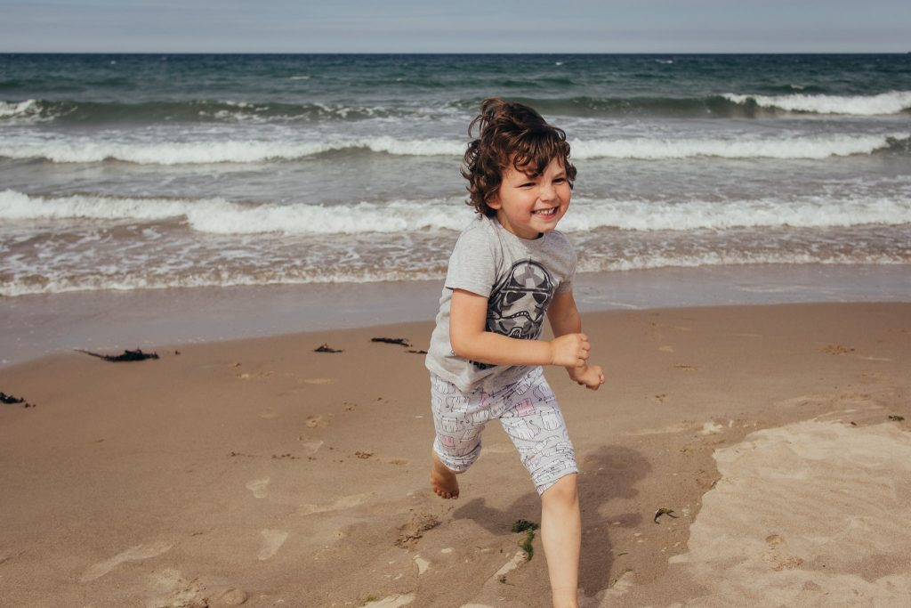 Boy running and smiling at Sandend Beach - Debbie Dee Photography - Aberdeenshire family photography
